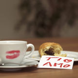 Cup of coffee with lipstick kiss, croissant and note Royalty Free Stock Photography