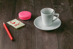 Cup of coffee with lipstick mark and note 'i love you' on table Royalty Free Stock Image