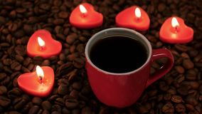 Cup coffee with lit candles in the shape of heart. Red small cup of black coffee with lit candles in the shape of heart, coffee beans laid out on the table and stock video footage