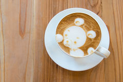 A cup of coffee with little bear pattern on wooden background Stock Images