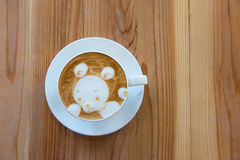 A cup of coffee with little bear pattern on wooden background Royalty Free Stock Images