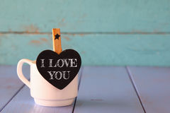 Cup of coffee and little heart shape chalkboard with the phrase: I LOVE YOU. Royalty Free Stock Photography