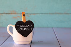 Cup of coffee and little heart shape chalkboard with the phrase: WEEKEND LOADING. Cup of coffee and little heart shape chalkboard with the phrase: WEEKEND Stock Photo