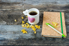 Cup with coffee/ Love cup and Note book on wooden background. Royalty Free Stock Photography
