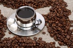 Cup of coffee with lump sugar and beans stock image