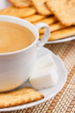 A cup of coffee with a lump sugar and crackers Stock Photo