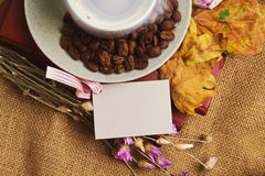 The cup of coffee lying on the books with maple leaves Stock Photography