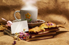 The cup of coffee lying ot the books with maple leaves Royalty Free Stock Image