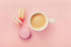 Cup of coffee with macaron on pink background from above, flat lay Royalty Free Stock Image