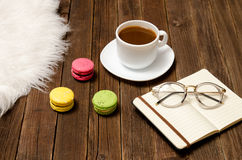 Cup of coffee, macarons, a notebook and glasses on a wooden table Stock Images