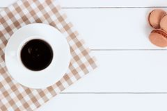Cup of coffee with macaroons on napkin and white background. Top view, copy space. stock photo