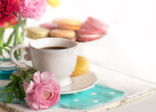 Cup of coffee. With macaroons on a table with flowers ranunculus Royalty Free Stock Image
