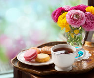 Cup of coffee. With macaroons on a table with flowers ranunculus Stock Photo