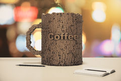 Cup of coffee made up of letters on a wooden table with diary Royalty Free Stock Images