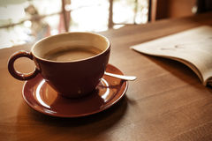 Cup of coffee and a magazine. On the table in the cafe. Toned photo Royalty Free Stock Images