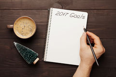 Cup of coffee and male hand writing in notebook goals for 2017 from above. Planning and motivation for the new year concept. Royalty Free Stock Photos