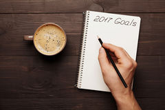 Cup of coffee and male hand writing in notebook goals for 2017. Planning and motivation for the new year concept. Top view. Cup of coffee and male hand writing royalty free stock photos