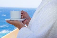 Cup of coffee in male hands over sea view Royalty Free Stock Image