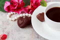A cup of coffee on a marble background next to pink flowers, white pearls, candy in the form of a heart. St. Valentine`s Day Stock Photo