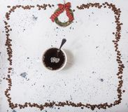 Cup of coffee with beans on a white marbled background. Cup of coffee with marshmallow and beans on a white marbled background. Top view with copyspace for your royalty free stock photo