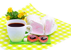 Cup of coffee with marshmallow, chocolate sweets, yellow wildflo Stock Photos