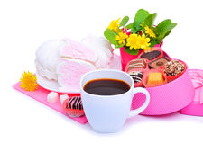 Cup of coffee with marshmallow, chocolate sweets, yellow wildflowers Stock Photography
