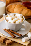 Cup of coffee with marshmallow, cinnamon sticks, brown sugar and croissant on wooden table. Stock Image