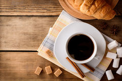 Cup of coffee with marshmallow, cinnamon sticks, brown sugar and croissant on wooden table. Royalty Free Stock Images