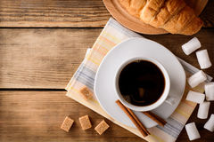 Cup of coffee with marshmallow, cinnamon sticks, brown sugar and croissant on wooden table. Stock Images