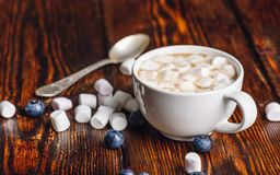 Cup of Coffee with Marshmallow. Cup of Coffee with Marshmallow with Scattered Few Blueberries and Some Marshmallows, and Spoon on Backdrop Stock Photography