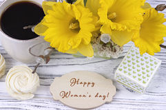 Cup of coffee with marshmallow, green gift box, yellow flowers on white wooden background and lettering happy women`s day english. Stock Photo