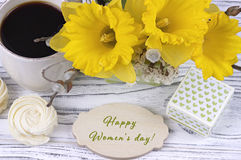 Cup of coffee with marshmallow, green gift box, yellow flowers on white wooden background and lettering happy women`s day english. Royalty Free Stock Photography