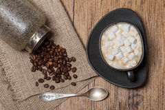 Cup of coffee with marshmallow, spoon and coffee beans in jar Royalty Free Stock Images