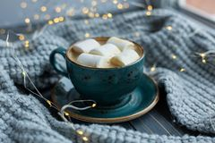Cup of coffee, marshmallow, warm knitted sweater on wooden background. Warm lights. Cozy winter morning. Lifestyle concept. Selective focus royalty free stock image