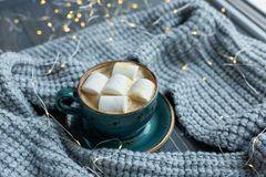 Cup of coffee, marshmallow, warm knitted sweater on wooden background. Warm lights. Cozy winter morning. Lifestyle concept. Selective focus royalty free stock photo