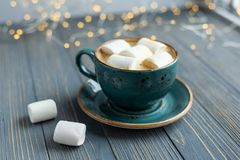 Cup of coffee, marshmallow on wooden background. Warm lights. Cozy winter morning. Lifestyle concept. Selective focus royalty free stock photo