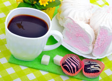Cup of coffee with marshmallows and chocolate candies on a green Royalty Free Stock Photo