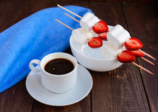 A cup of coffee and marshmallows with fresh strawberries on skewers Stock Images