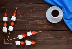 A cup of coffee and marshmallows with fresh strawberries on skewers on a wooden background. Royalty Free Stock Photography