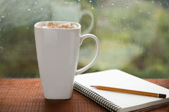 Cup coffee with marshmallows and a notebook. Of coon a rainy day window background Stock Photography