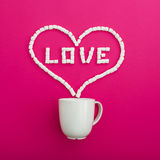 Cup of coffee and marshmallows on pink background. Heart symbol and quote Love. Flat lay. Top view. Cup of coffee and marshmallows on pink background. Heart stock images