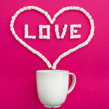 Cup of coffee and marshmallows on pink background. Heart symbol and quote Love. Flat lay. Top view. Cup of coffee and marshmallows on pink background. Heart royalty free stock image
