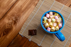 Cup of coffee with marshmallows. On the wood background Stock Photos
