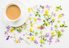 Cup of coffee with milk on the background of small flowers and leaves. Cute simple background. Floral backdrop for banners, cards, covers. The theme of the Royalty Free Stock Image