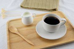 A cup of coffee, milk and butter cake on wooden plate. With flower on white bed, selective focus on coffee stock image