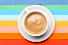 Cup of coffee with milk or cappuccino beverage on colorful as rainbow background. Dose of energy concept. Coffee on. Colorful positive background, top view Royalty Free Stock Images