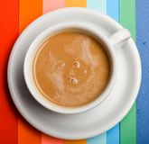 Cup of coffee with milk or cappuccino beverage on colorful as rainbow background. Drink with caffeine or cocoa with milk. Coffee on colorful positive Royalty Free Stock Image