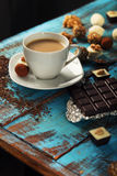Cup of coffee with milk, chocolate bar and variety candies Stock Image