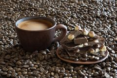 Cup of coffee and milk chocolate among coffee beans royalty free stock photography