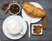 Cup of coffee with milk foam and biscuits and coffee beans lying on a black stone stand, top view. Delicious breakfast Royalty Free Stock Images